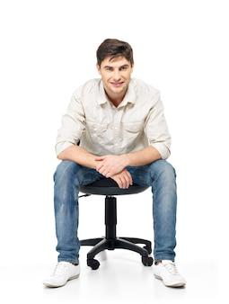 웃는 행복 한 남자의 초상화는 흰색 절연 사무실의 자에 앉아있다.