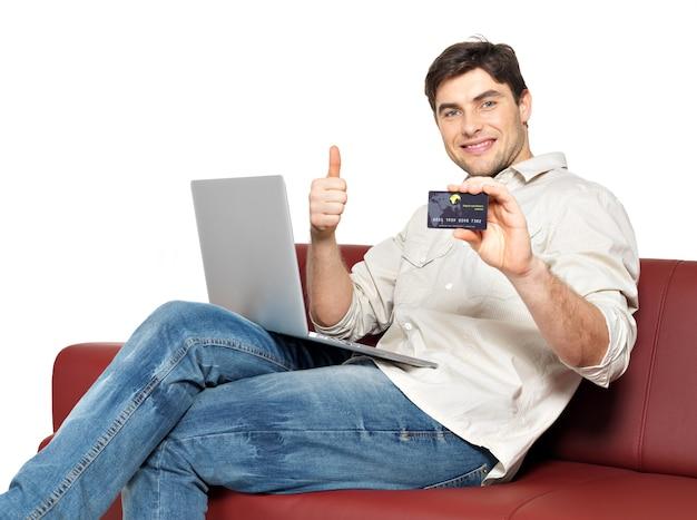 ノートパソコンで幸せな男の笑顔の肖像画は親指をあきらめ、白で隔離のクレジットカードを示しています。