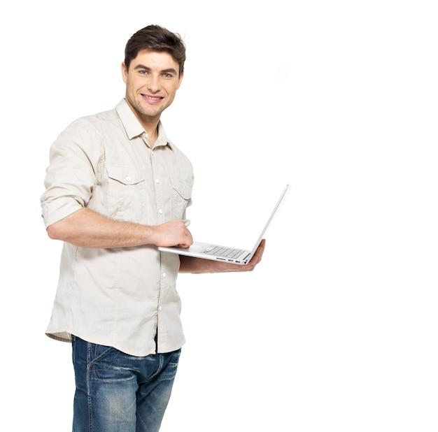 カジュアルなノートパソコンで笑顔の幸せな男の肖像画-白で隔離。コンセプトコミュニケーション。