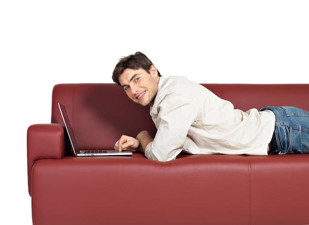 白で隔離、ソファの上のラップトップと笑顔の幸せな男の肖像画。