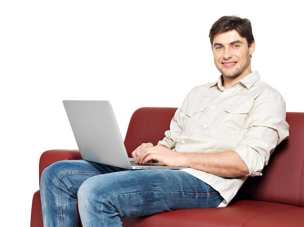 ラップトップと笑顔の幸せな男の肖像画は、白で隔離のソファに座っています。