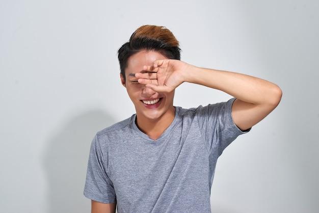 Портрет улыбающегося счастливого спортивного человека в футболке на сером фоне студии