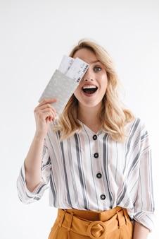Портрет улыбающейся счастливой женщины в повседневной одежде, держащей проездные билеты и паспорт, изолированные на белой стене