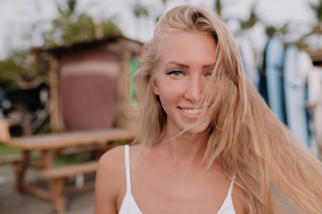 Портрет улыбающейся счастливой женщины с длинными развевающимися волосами и очаровательной улыбкой