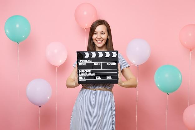 화려한 공기 풍선이 있는 분홍색 배경에 고전적인 검은색 필름을 만드는 클래퍼보드를 들고 파란 드레스를 입고 웃고 있는 행복한 젊은 여성의 초상화. 생일 휴가 파티, 사람들은 진심 어린 감정.