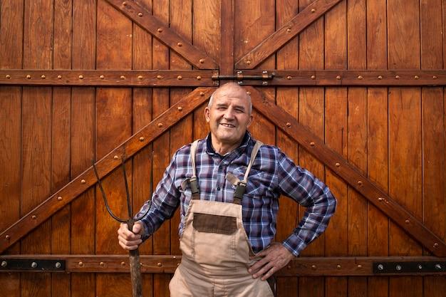熊手道具を持って、家畜農場で木造の納屋または食糧穀倉のドアのそばに立っている笑顔の勤勉な農夫の肖像画。
