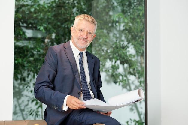 Портрет улыбающегося главного инженера с взглядом проекта здания