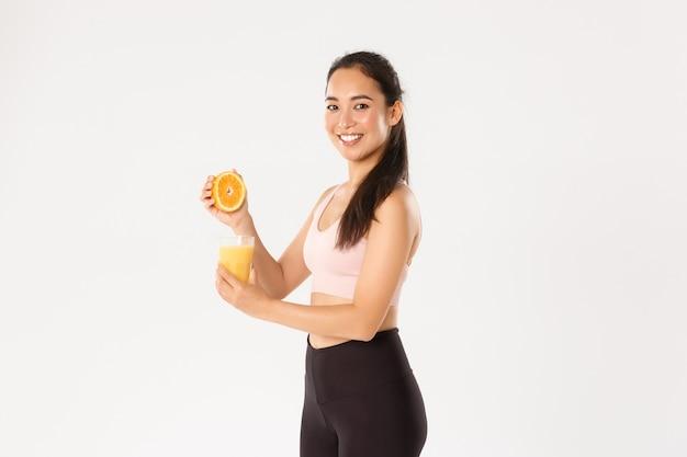 Портрет улыбающейся здоровой и стройной азиатской девушки советует есть здоровую пищу на завтрак, набираться энергии для хорошей тренировки, выжимая апельсиновый сок в стакане.