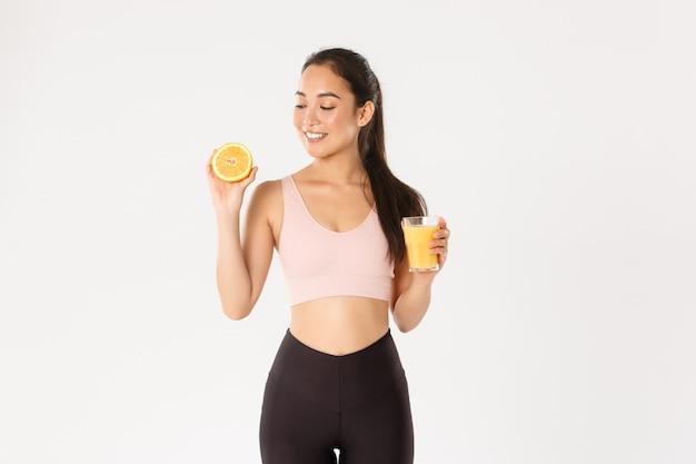 Портрет улыбающейся здоровой и стройной азиатской девушки советует есть здоровую пищу на завтрак, набирать энергию для тренировки, держать свежий сок и апельсин.