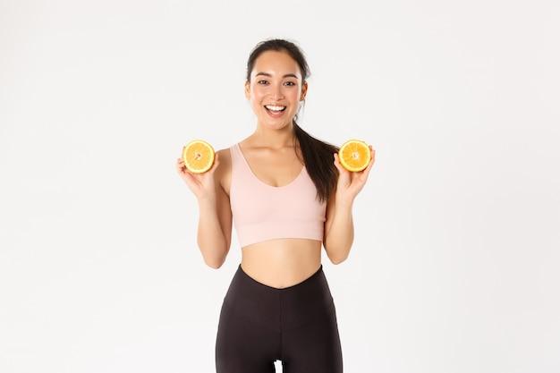 Портрет улыбающейся здоровой и стройной азиатской девушки советует есть здоровую пищу на завтрак, набирать энергию для тренировки, держать две половинки апельсина.