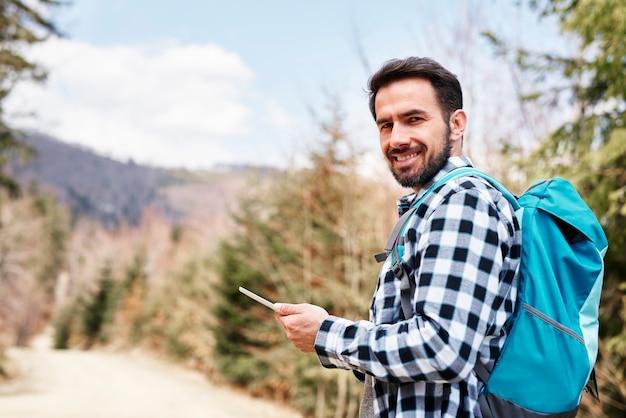 ハイキング旅行中に携帯電話を使用して笑顔のハイカーの肖像画