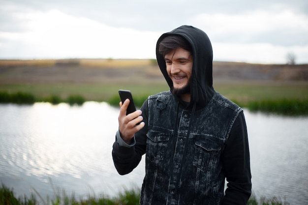 Портрет улыбающегося человека с капюшоном, смотрящего в смартфон, за пределами реки.