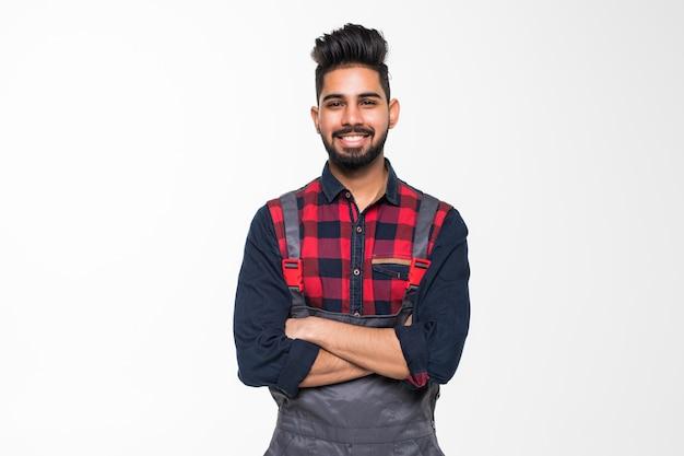 Портрет улыбающегося индийский мужчина работника в синей форме, изолированных на пустое пространство Premium Фотографии