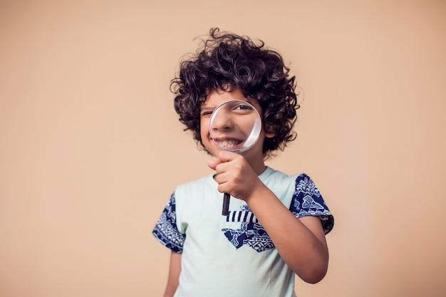 돋보기 유리를 잡고 웃는 아이 소년의 초상화. 어린이와 교육 개념