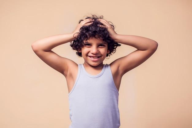 곱슬 머리를 가진 웃는 아이 소년의 초상화입니다. 어린이 감정 개념