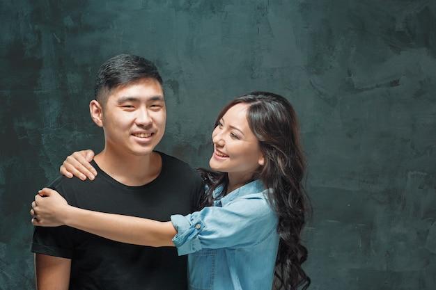 Портрет улыбающейся корейской пары на фоне серой студии