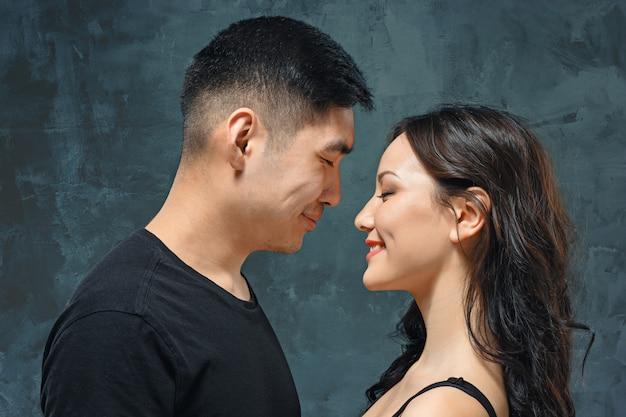 Портрет улыбающегося корейской пары на сером