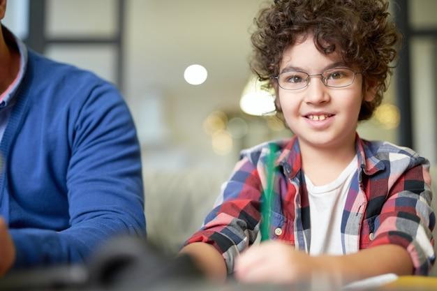 彼の父と一緒に机に座って、家で宿題をしながらメモをとっている眼鏡をかけて笑顔のラテン系の少年の肖像画。オンライン教育、ホームスクーリングの概念