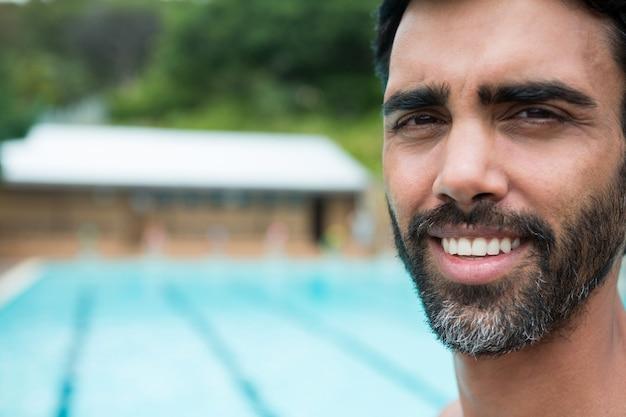 Портрет улыбающегося спасателя, стоящего у бассейна