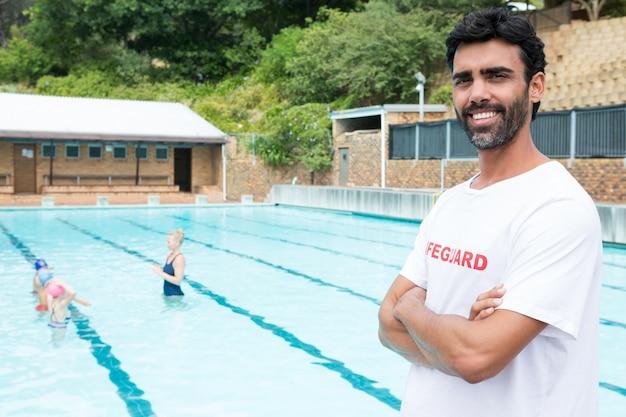 Портрет улыбающегося спасателя, стоящего со скрещенными руками у бассейна