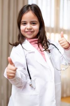 親指をあきらめる医者に扮した笑顔の小さな子供の肖像画
