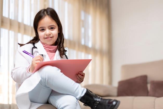 医者の制服の手書きのレポートに身を包んだ笑顔の小さな子供の肖像画