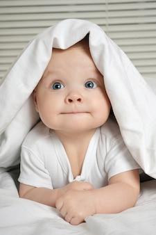 Портрет улыбающегося маленького ребенка, лежащего в своей кроватке