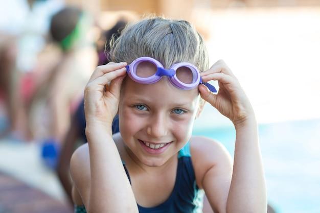 수영 고글을 들고 웃는 어린 소녀의 초상화