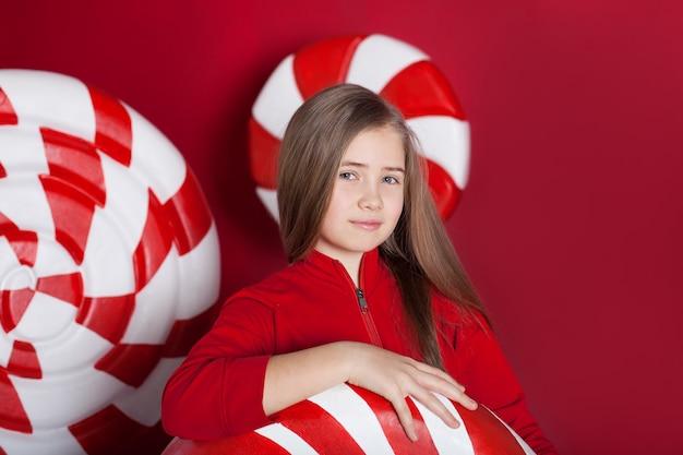 赤い背景の上の大きなクリスマスキャンディーと笑顔の少女の肖像画