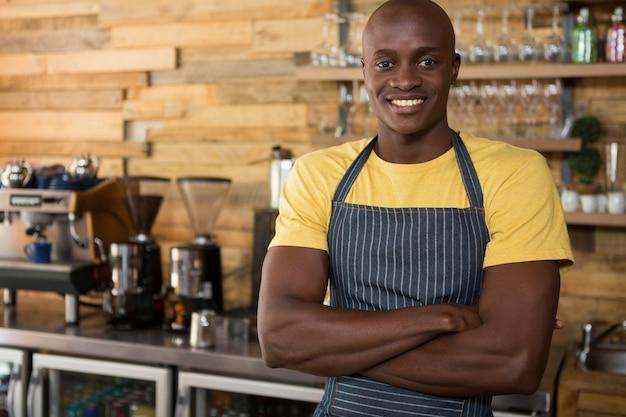 コーヒーショップで交差した腕を組んで笑顔の男性バリスタの肖像画