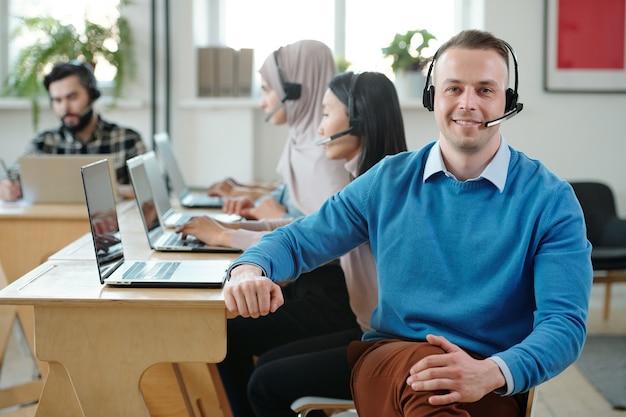 オンラインで顧客と一緒に働いている同僚に対して足を組んで座っているマイクとヘッドセットで笑顔の男性のコールセンターのオペレーターの肖像画