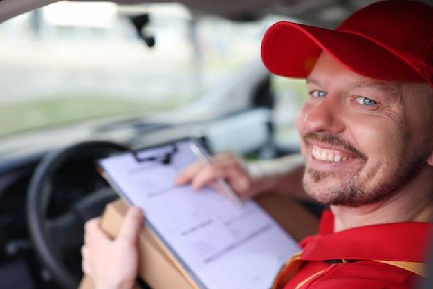 문서와 함께 자동차 살롱에서 웃는 남성 택배 드라이버의 초상화