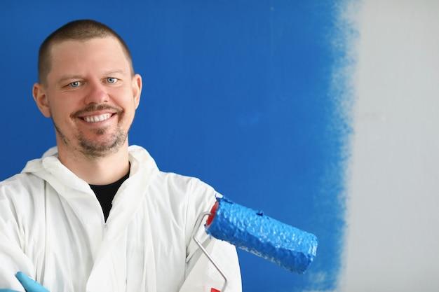 壁を塗るためのローラーを保持している笑顔の男性の家の画家の肖像画