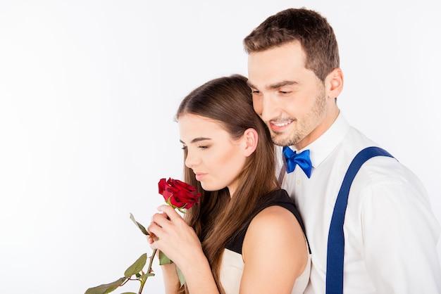 赤いバラを保持している笑顔の男性と魅力的な女性の肖像画