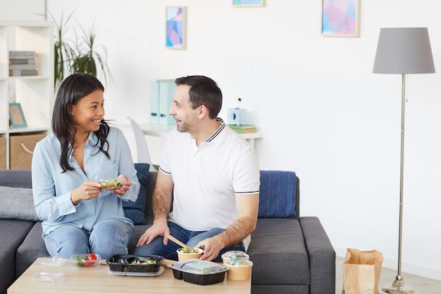 Портрет улыбающегося мужчины и женщины, весело болтающих, наслаждаясь обедом на вынос в офисе или дома