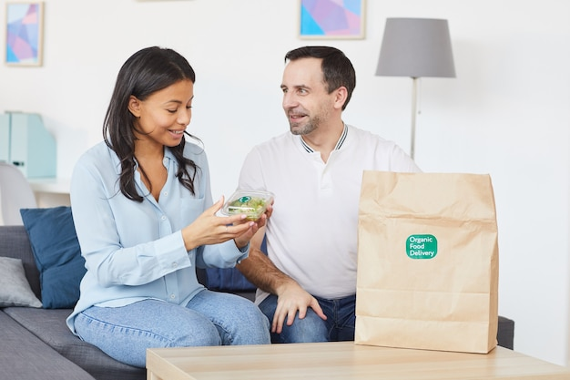 Портрет улыбающегося мужчины и женщины, открывающих сумку для доставки еды, наслаждаясь обедом на вынос в офисе или дома