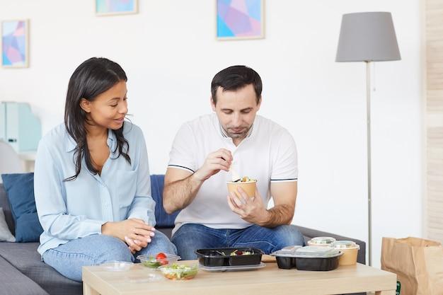 Портрет улыбающегося мужчины и женщины, открывающих контейнеры для доставки еды, наслаждаясь обедом на вынос в офисе или дома