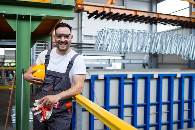 Портрет улыбающегося человека фабричного рабочего, стоящего в производственном цехе
