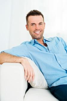 ソファの上の笑顔の男の肖像画