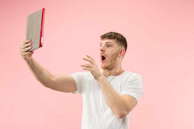 ピンクのスタジオで隔離の空白の画面でノートパソコンを指して笑顔の男の肖像画。