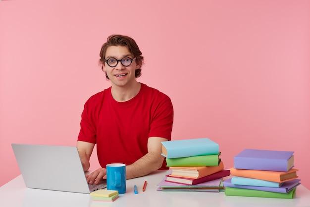 Портрет улыбающегося студента в очках в красной футболке, сидит у стола и работает с тетрадью и книгами, подготовлен к экзамену, широко улыбается, изолированные на розовом фоне.