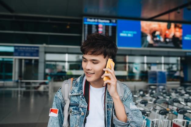 공항에서 택시를 기다리는 동안 문자를 보내는 웃는 남자의 초상화