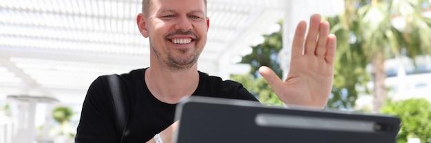 열대 지방에 밖에 앉아 있는 동안 태블릿 화면에 손을 흔드는 웃는 남자의 초상화