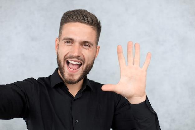 Портрет улыбающегося человека с поднятой рукой в приветствии. дай пять концепции.