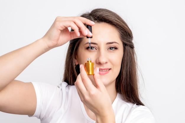 Портрет улыбающегося мастера маникюра держит бутылку золотого лака для ногтей над глазом на белой стене
