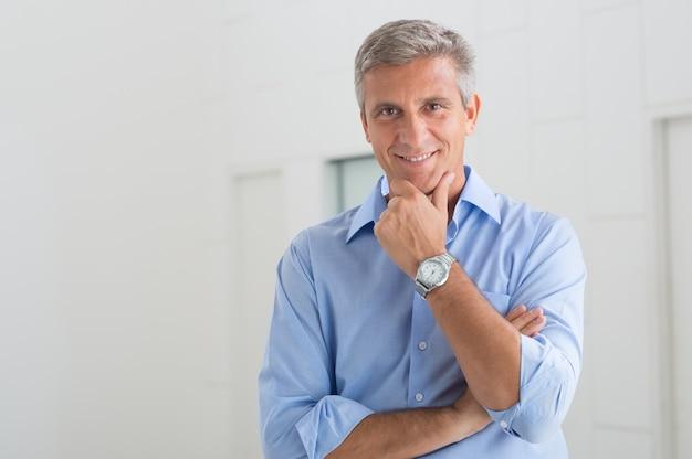 Портрет улыбающегося зрелого бизнесмена с рукой на подбородке