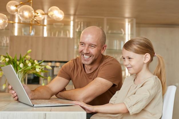 아늑한 가정 내부에서 가족과 화상 채팅으로 말하는 동안 성숙한 아버지와 어린 소녀가 함께 노트북을 사용하는 미소의 초상화
