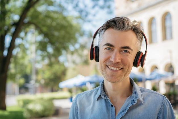 赤いヘッドフォンを身に着けている音楽を聴いて笑顔の成熟した男の肖像画