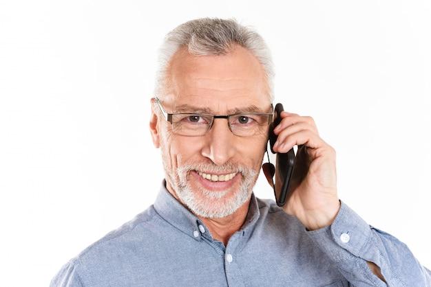 分離されたスマートフォンで話している成熟した男の笑顔のポートレート