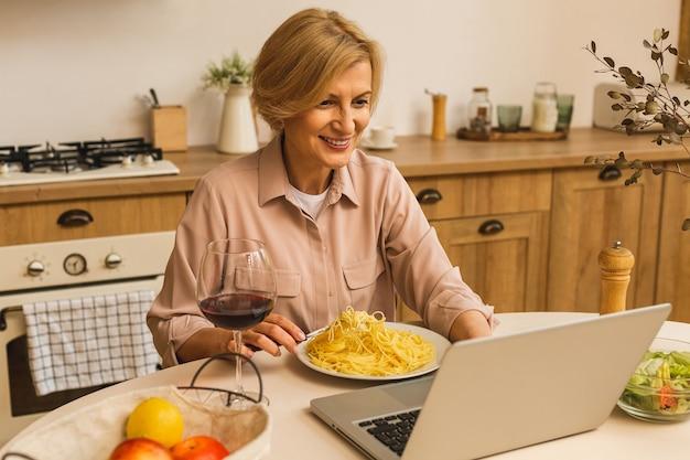 台所のテーブルでラップトップを使用しながらワインのグラスを保持している笑顔の成熟した年配の女性の肖像画。フリーランス在宅勤務のコンセプト。